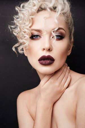 Portrait of a beautiful young woman with bright makeup and curly blond hair. Fashionable model girl with dark full lips and smokey eyes, with perfect smooth skin and sensual facial expression Standard-Bild - 140470237
