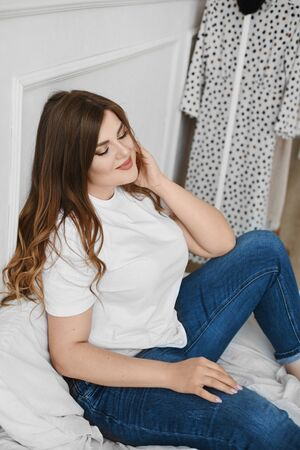 Happy plus-size model girl in jeans and white t-shirt sitting on the bed in the morning. Young plump woman in a casual outfit posing on the bed. Body positive. Concept of unideal beauty. XXXL fashion Standard-Bild - 139189995