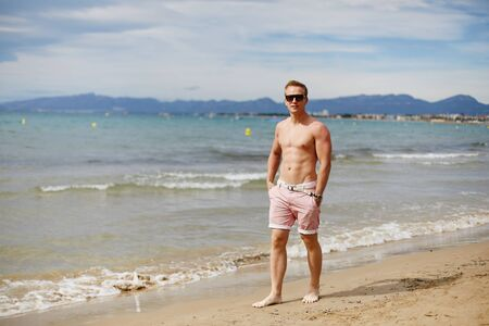 Handsome shirtless athletic young guy walking on the beach by the waterline. Young muscular man with perfect body in shorts and sunglasses walking by the sea coast. Travel fashion. Sport lifestyle Archivio Fotografico
