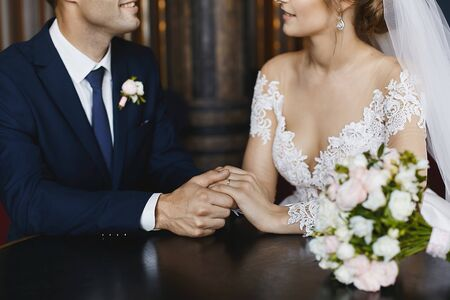 Young bride in an elegant lace dress and handsome groom holding hands together at the table of a cafe. Closeup photo of beautiful female and male hands. Young wedding couple after the bridal ceremony. 免版税图像