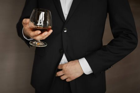 Young businessman in official black suit holding glass of cognac. Close up of male hand holding glass of cognac. Man is standing in elegant suit Reklamní fotografie