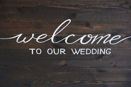 Wooden board with the inscription Welcome to our wedding. White lettering on a dark wooden surface - welcome to our wedding. Greeting inscription on a brown wooden plank - welcome to our wedding. Banque d'images - 140644292