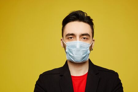 Portrait of handsome young man in black protective mask looking in camera, isolated on yellow background. Seasonal illness and seasonal flu prevention. Standard-Bild - 143295049