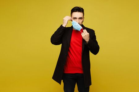 Young man in black coat putting a medical protective mask on, isolated at the yellow background with copy space for your text. Concept of healthcare.
