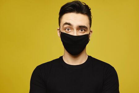 Handsome man in black t-shirt and black protective mask isolated on yellow background. Seasonal illness, and seasonal flu concept. Healthcare lifestyle concept Standard-Bild - 143295092