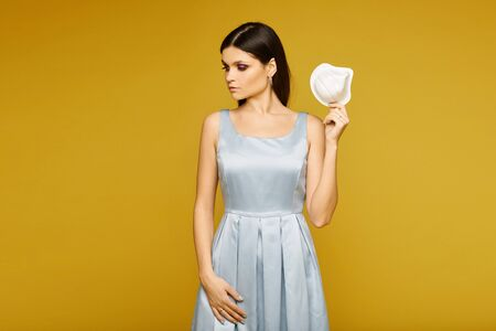 Young woman in dress looking aside and posing with a respirator in her hand on yellow background, isolated. Concept of protection against the flu epidemic, dust allergy and air pollution Standard-Bild - 143296562