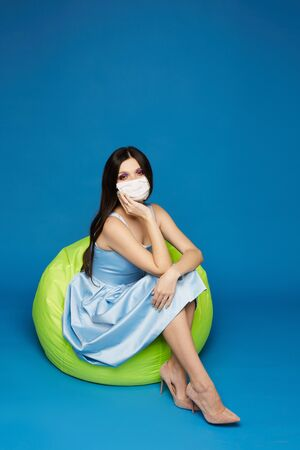 Young woman in dress and protective mask looking in the camera and posing in full length at the blue background, isolated. Concept of protection against the flu epidemic Standard-Bild - 143296578