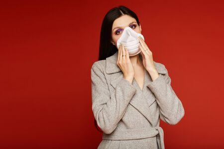 Young woman in coat and respirator looking in the camera and posing at the red background, isolated. Concept of protection against the flu epidemic, dust allergy and air pollution Standard-Bild - 143296629