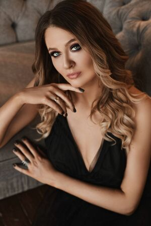 Young woman with blond hair and perfect trendy makeup. Beautiful blonde model girl with modish makeup, deep eyes and seductive look. Concept of modish official makeup and smooth skin Standard-Bild - 143296631