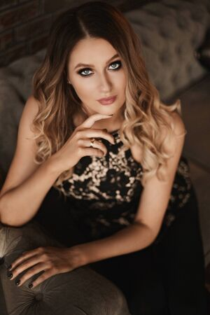 Young woman with blond hair and perfect trendy makeup. Beautiful blonde model girl with modish makeup, deep blue eyes and seductive look. Concept of modish official makeup and smooth skin Standard-Bild - 143296632