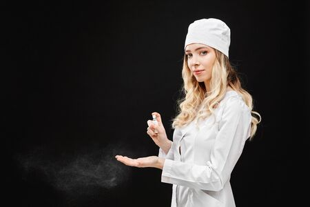 Young woman in medical uniform using hand sanitizer spray, isolated at black background. Hand hygiene and antibacterial protection. Stock fotó
