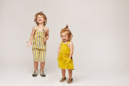 Two cute stylish children, boy and girl in fashionable summer clothes posing on a beige background. Isolated in full length with copy space
