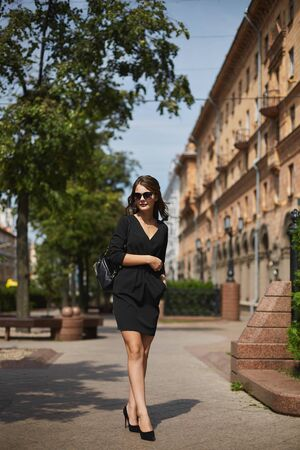 Beautiful brunette young woman wearing a dress walking on the street. Summer fashion