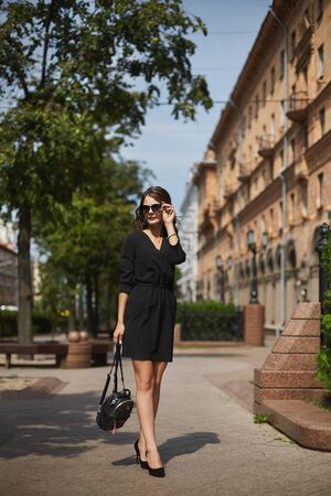 Beautiful young business lady wearing a black dress walking on the street. Confident fashion, official style