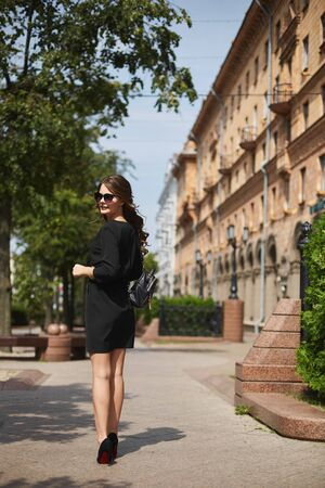 Gorgeous young model woman in black dress looking at camera and posing with back in the city