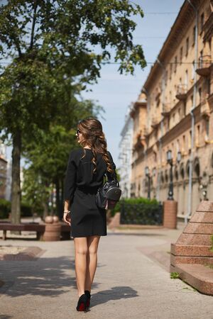 Beautiful elegant woman wearing hat and flattering dress in the street. Lady fashion street concept Standard-Bild