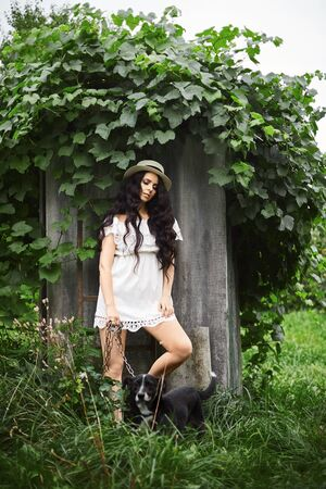 Brunette young woman in short white dress and straw hat posing with the dog posing outdoors. Model girl in short rustic dress. Spring nature. Summertime. Summer fashion