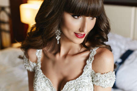 Closeup portrait of a gorgeous young bride with wedding hairstyle and red lips in bridal dress. Young woman in a luxury wedding dress decorated with crystals. Wedding fashion