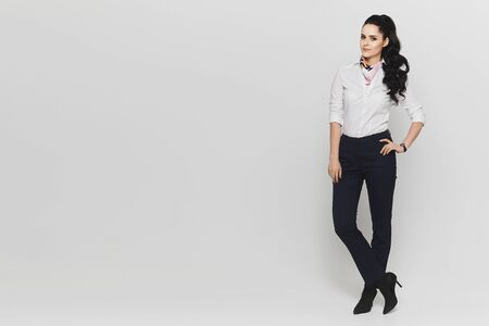 Portrait in the full length of a young woman in white blouse and in dark pants isolated at white background. Copy space on the left Standard-Bild