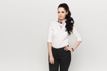 A young woman in white blouse and dark pants isolated at white background. Female office worker on white background. Official style fashion concept
