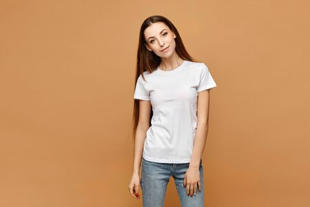 Young woman in white blank t-shirt and blue jeans isolated at beige background, studio close-up. Model girl in a casual outfit. Isolated with copy space