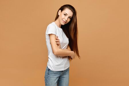 Beautiful girl with slim body in white blank shirt and blue jeans posing with folded hands at the beige background, isolated. Copy space for advertisement