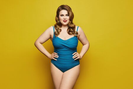 Plus-size model girl with stylish hairstyle and red lips in fashionable swimsuit at the yellow background, isolated. Fat woman in swimsuit on yellow background.