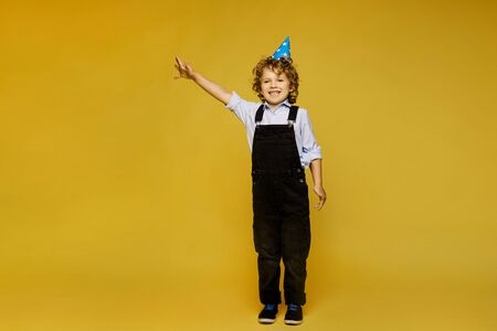 Stylish red-haired little boy in overalls and birthday cap posing at the yellow background, isolated. Kids fashion