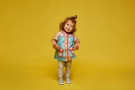 Cute little girl in a modish raincoat and rubber boots isolated at the yellow background. Child fashion. Copy space Standard-Bild