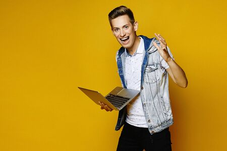 Beaming positive guy with laptop in his hands over yellow background. Young hipster with notebook isolated at yellow background. Remote work concept