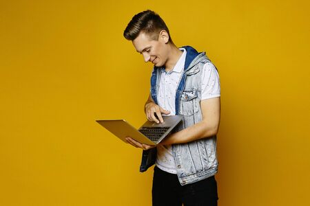 Smiling stylish guy in casual outfit posing with laptop on yellow-orange background, isolated. Young handsome man with notebook in the hands. Mockup copy space