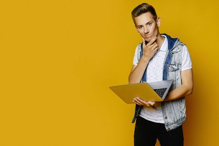 Thoughtful young man in casual outfit is holding a laptop and looking in camera on yellow background, isolated. Concept of remote worker. Mockup with copy space