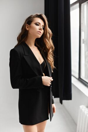 Sexy brunette model girl in black oversized blazer posing at white interior. Fashion and beauty Standard-Bild