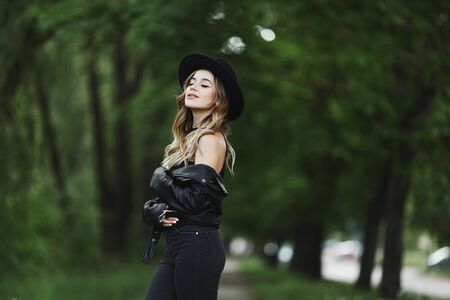 Side view of a beautiful girl in leather jacket and black hat enjoying a summer day on a green city street. Standard-Bild