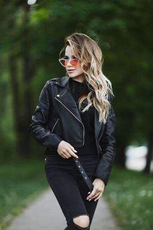 Young woman in a leather jacket and fashionable sunglasses is walking alone outdoors in summer day Standard-Bild