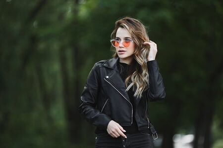 Young beautiful girl in a leather jacket and fashionable sunglasses is walking alone outdoors in summer day