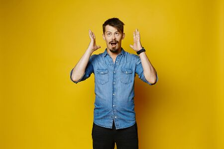 Young guy with beard and mustache pointing finger and looking in the camera, isolated over yellow background. Young emotional hipster