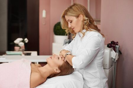 Female doctor preparing a young woman for non-surgical facelifting procedure. A rejuvenating cosmetic care treatment in aesthetic medicine clinic.