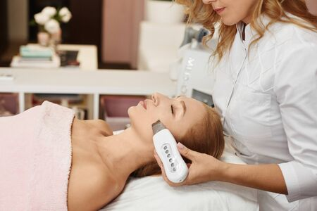 Beautiful woman getting face peeling procedure in a beauty clinic, non-surgical facelifting procedure. Rejuvenating facial treatment