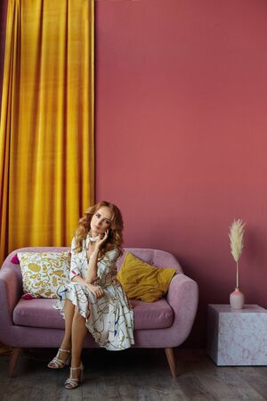 Slim model girl in a summer dress sits on the couch in the home interior. Concept of summer fashion