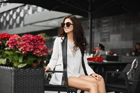 Young fashionable woman in stylish outfit and sunglasses posing outdoors at a cafe table in summer day.