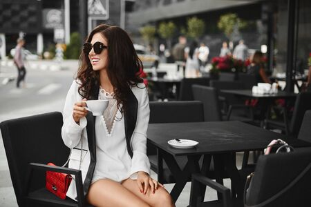 Young woman in stylish outfit and sunglasses drinks coffee outdoors at a cafe table in summer day.