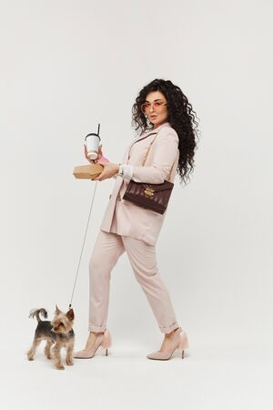 Young fashionable woman walking with a york terrier dog with coffee cup in her hand. Fancy curly hairstyle. Urban fashion style concept
