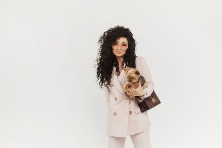 Stylish girl in official outfit holding cute little dog in her hands and posing on white background, isolated. Urban fashion concept.