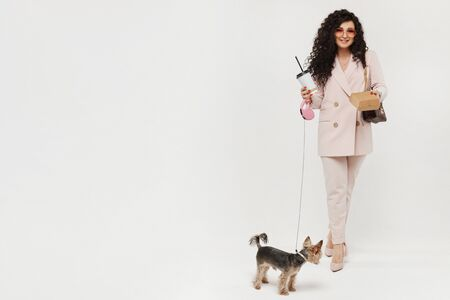 Modish woman with a plastic cup of coffee and cute little dog walking on white background, isolated. Urban fashion concept mockup.