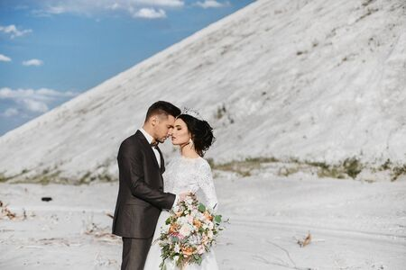 A young handsome groom and stylish bride hugging outdoor with a beautiful landscape at background