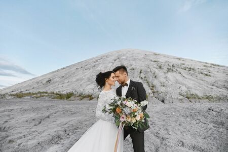 Happy wedding couple standing outdoors over the beautiful landscape with mountains Standard-Bild