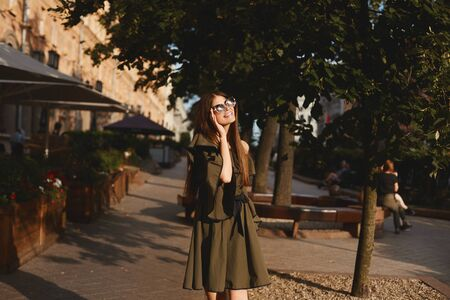 Portrait of a cheerful young woman in dress touching her sunglasses on urban background. Fashionable girl with beautiful brown hair smiling to camera. Standard-Bild