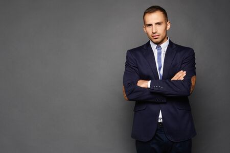 Confident businessman in suit isolated at dark background. A handsome young man in an official outfit standing with crossed arms. Standard-Bild