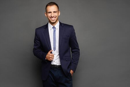 Happy businessman in suit isolated at dark background. A handsome young man in an official outfit posing at the grey background. Standard-Bild